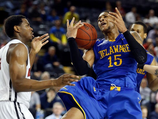 Delaware forward Maurice Jeffers (right) is fouled by Northeastern's Reggie Spencer in the second half of Delaware's 67-64 loss in a CAA tournament quarterfinal at the Royal Farms Arena in Baltimore on Saturday.