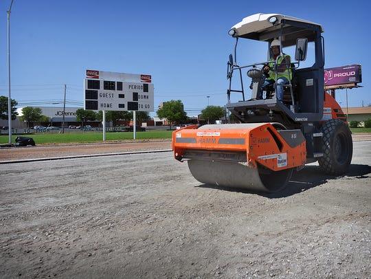 A Hellas Construction Inc. employee drives a compacter