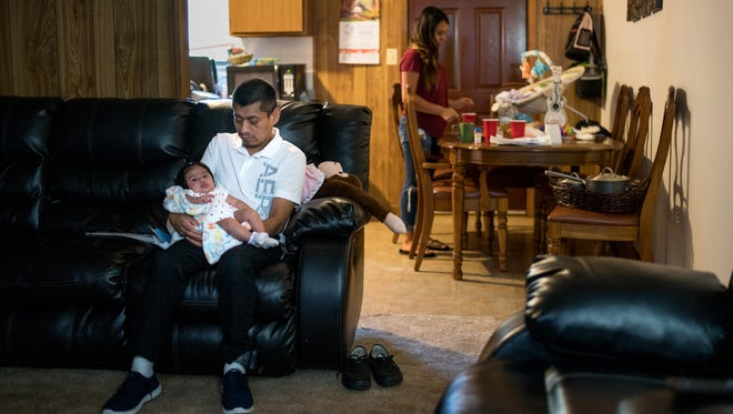 Alina Delapaz, right, cleans her kitchen Wednesday, July 18, 2018, as Gonzalo Chavez holds her 3-month-old daughter, Itzayana, at her home in Morristown, Tenn. Chavez, who was detained during an immigration raid April 5 and recently released, is staying with Delapaz after losing his apartment while in custody.