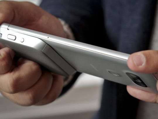 This Feb. 11, 2016, photo, shows a camera grip, at bottom left, with physical buttons to take the photos and record video with the LG G5 phone, in New York. The grip connects to the phone's bottom. LG is dipping its toes into a modular-design concept with its upcoming G5 smartphone. (AP Photo/Bebeto Matthews)