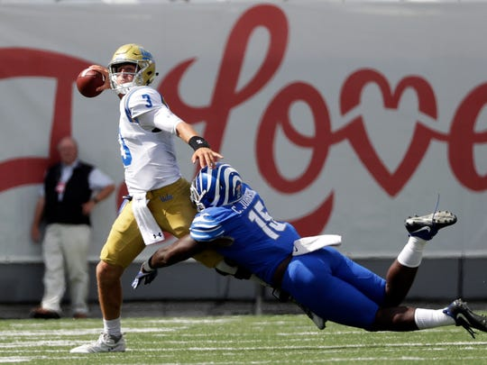 UCLA quarterback Josh Rosen (3) passes as he is hit by Memphis defensive lineman Christian Johnson (15) in the second half of an NCAA college football game Saturday, Sept. 16, 2017, in Memphis, Tenn. Memphis upset UCLA 48-45. (AP Photo/Mark Humphrey)