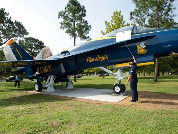 Members of the F/A-18 restoration crew help to unveil the new jet memorial near the front gate of the Pensacola Naval Air Station Tuesday morning July 1, 2014. The F/A-18 now on display replaces the old F-11 that had been on display at the site since 1965.