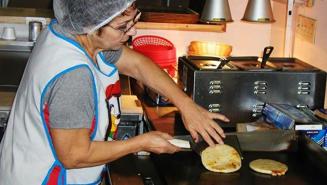 Workers at Pupuseria Gladys prepare a pupuseria.
