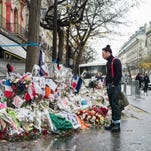 Jesse Hughes (R), the frontman of the U.S. band 'Eagles of Death Metal', pays his respects to the victims of the 13th November Attacks in front of the Bataclan in Paris, France, on December 8, 2015.