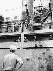 Officers and crew of the USS Liberty survey damage to the ship suffered during a June 8, 1967, attack in the Mediterranean.