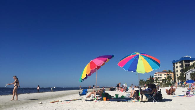 In this Sunday, November 19, 2017 photo, people gather to enjoy the beautiful weather on Fort Myers Beach.