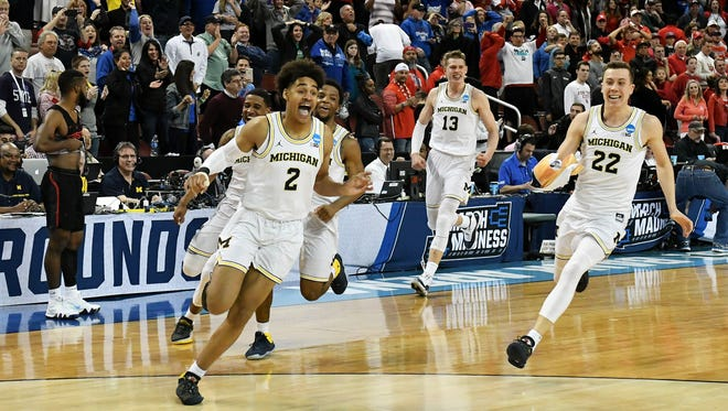 Jordan Poole runs in celebration with his teammates after Poole's 3-pointer defeated Houston.