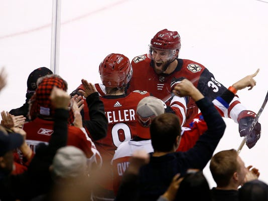 Arizona Coyotes center Clayton Keller, middle, celebrates his overtime against the Washington Capitals with defenseman Alex Goligoski (33) in an NHL hockey game, Friday, Dec. 22, 2017, in Glendale, Ariz. The Coyotes defeated the Capitals 3-2. (AP Photo/Ross D. Franklin)
