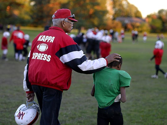 Willard Walker, 80, area civil rights leader, public servant and Kappa Express football program founding member and head coach, helps a young   Kappa Express player who was slightly injured at   practice at St. Joseph Park in Lansing Thursday  10/9/2014  .     (Lansing State Journal | Rod Sanford)