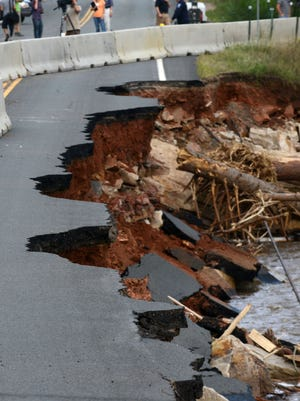 Photographers capture the damage to U.S. Highway 34 caused by the flooding of the Big Thompson River, bottom, near the Big Thompson Elementary School, in 2013.