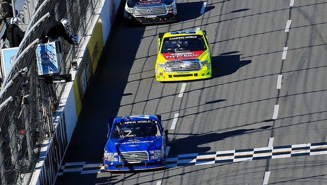 Joey Logano (29) takes the checkered flag to win Saturday's Kroger 250 at Martinsville Speedway.