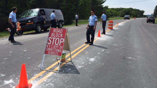 New York Department o Correctional Services officers conduct a roadblock along New York State Route in Cadyville Sunday.