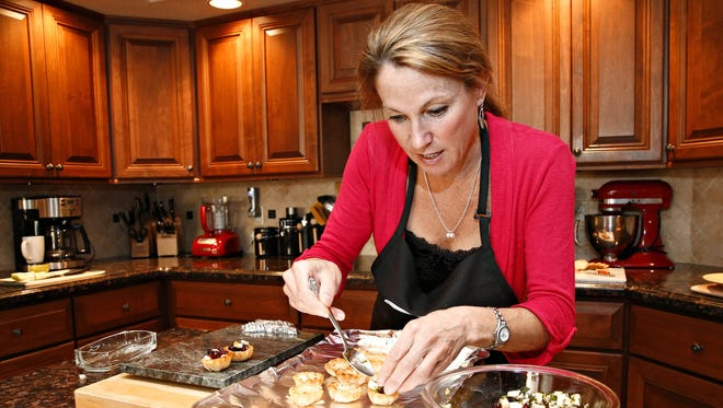 Robin Miller fills Brie Tartlets with Cranberry-Apple Relish in her Scottsdale kitchen.