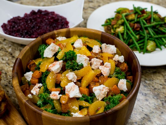 A salad of butternut squash, clementine, and kale topped