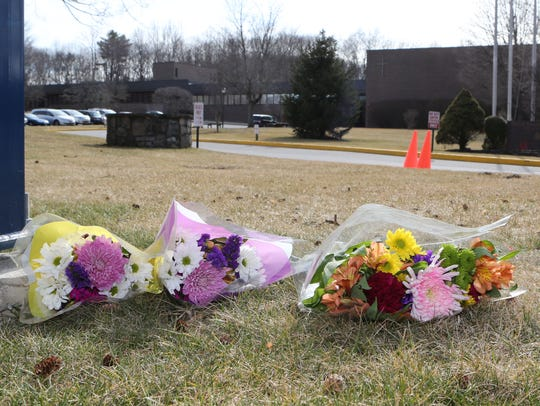 Flowers lay at the entrance to Kennedy Catholic High