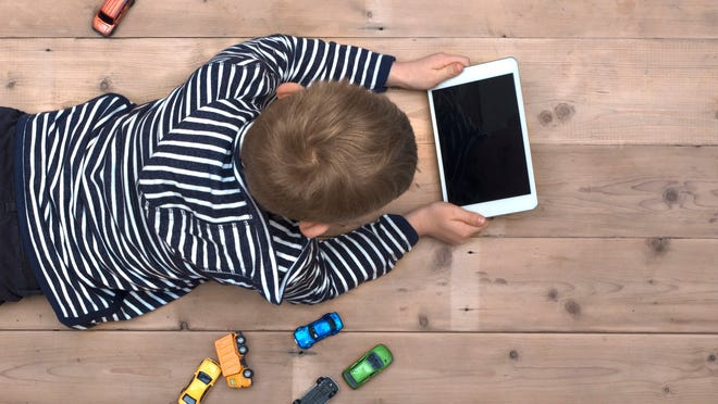 A boy laying on the floor with a tablet computer with toy cars lying at his side.