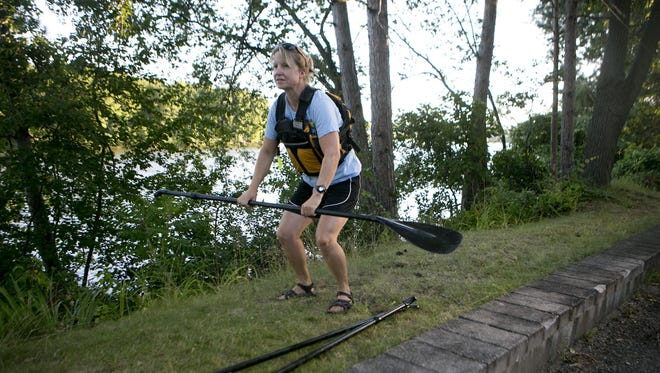 SUP the Rapids owner Kim Kinsey demonstrates how to stand up while paddleboarding before taking out a group of paddleboarders in Wisconsin Rapids, Friday, July 31, 2015.