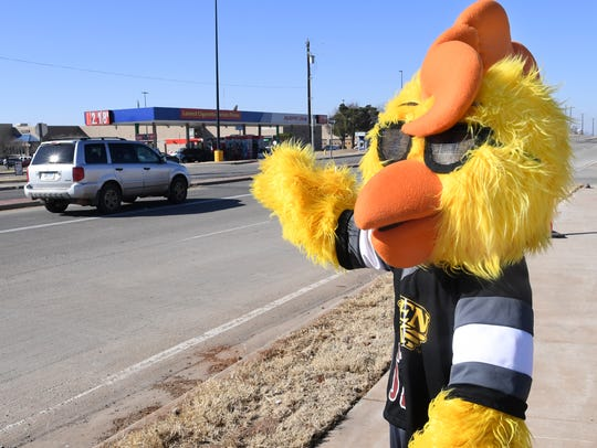 Clucky the Golden Chick mascot waved as traffic passed