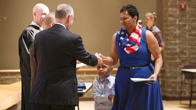 Alexi Voladamu of Fiji accepts a certificate after taking the Naturalization Oath of Allegiance to the United States of America at Missouri State University on Wednesday. Her son Daniel Harlem, 3, ran up to her as she approached the stage.