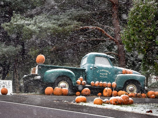 Snow falls on a display of pumpkins for sale along