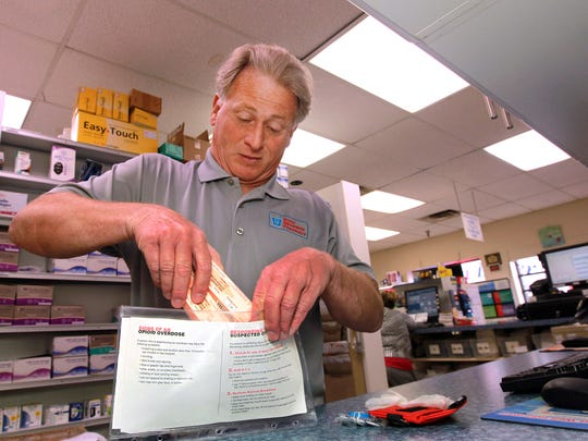 Pharmacist Sam Coletta places boxes containing vials of naloxone into an opioid overdose kit on June 13 at Avenue Pharmacy, Dayton, Ky., which he owns.