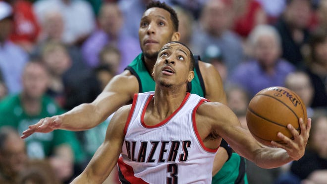 Portland Trail Blazers guard C.J. McCollum, right, shoots over Boston Celtics guard Evan Turner, left, during the first half of an NBA basketball game in Portland, Ore., Thursday, March 31, 2016.