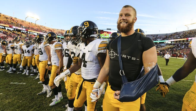Iowa's Drew Ott (arm in sling) joins the team for celebration after the 31-17 victory against Iowa State.