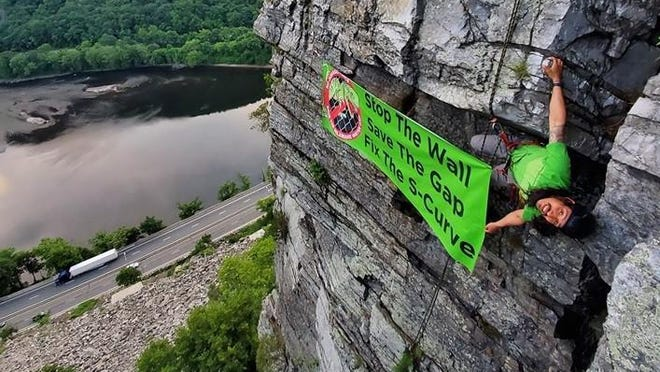 "A climber brandishes a banner calling to ""Stop The Wall Save The Gap Fix The S-Curve"" while suspended from a cliff overlooking the Delaware Water Gap."