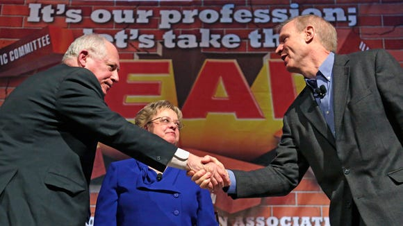 Illinois Gov. Pat Quinn, left, and his Republican rival, businessman Bruce Rauner, shake hands in April after they appeared together at the annual meeting of the Illinois Education Association in Chicago.