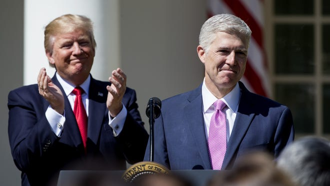 U.S. Supreme Court Justice Judge Neil Gorsuch speaks as President Trump looks on during a ceremony in the Rose Garden at the White House April 10, 2017 in Washington.