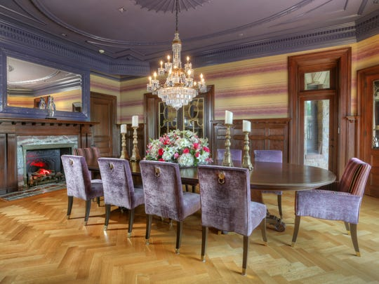 The dining room features a  hearingbone hardwood floor, guilded filagree mirror doors and the original fireplace, fully restored.
