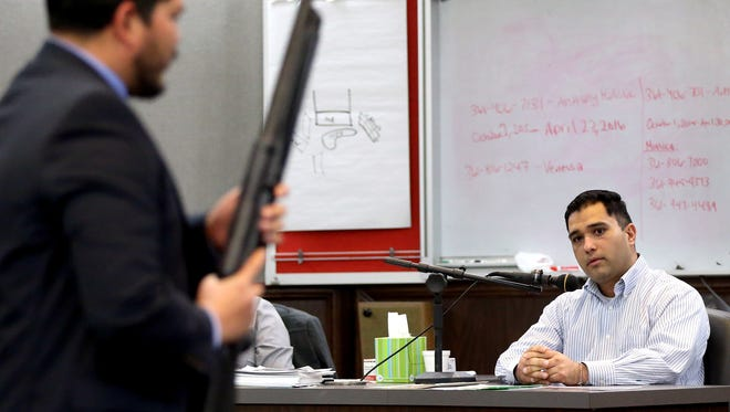 Anthony Molina talks to District Attorney Mark Gonzalez as he holds the weapon Molina used during his trial on Wednesday, Feb.16, 2017, at the 214th District Court in Corpus Christi.