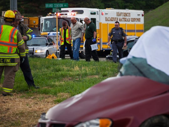 Emergency responders walk on either side of an injured