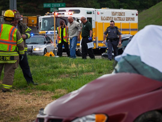 Emergency responders walk on either side of an injured man as they help him toward a waiting ambulance at the scene of a two-vehicle accident that left two people dead off of Jefferson Highway in Staunton on Monday, April 20, 2015.
