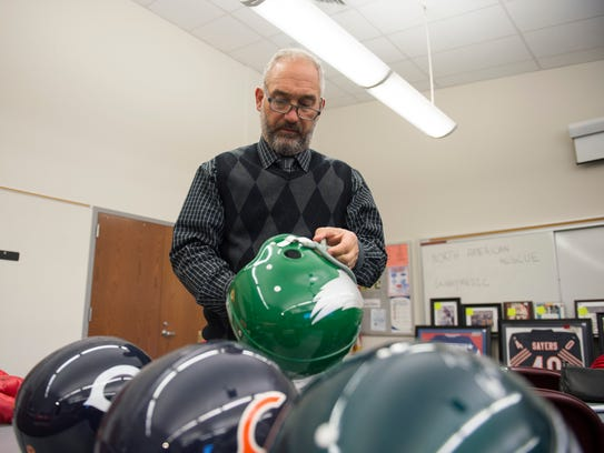 Auctioneer Alfred Finocchiaro looks over a vintage Eagles helmet signed by Chuck Bednarik. It's for sale at an auction of items seized by the Burlington County Prosecutor's Office.