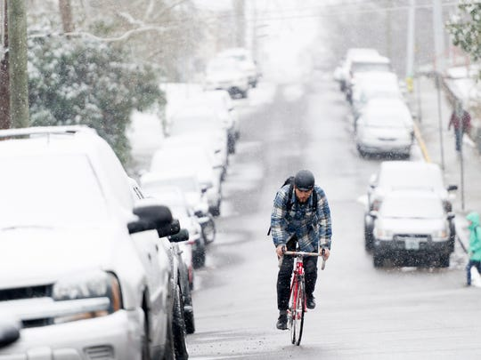 UT senior Marlow Payat, of Memphis, bikes along Laurel Avenue during an afternoon snowfall in Knoxville on Tuesday, Jan. 16, 2018.
