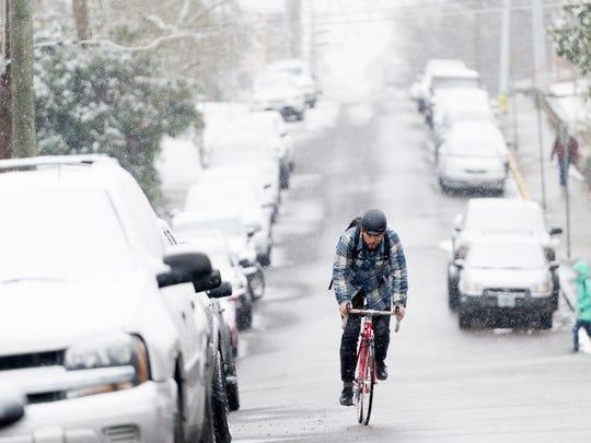 UT senior Marlow Payat, of Memphis, bikes along Laurel Ave during an afternoon snowfall in Knoxville, Tenn., on Tuesday, Jan. 16, 2018.