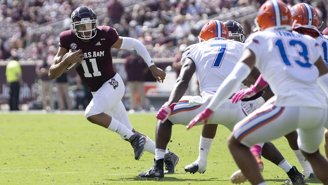 Texas A&M quarterback Kellen Mond looks to run against Florida linebacker Jeremiah Moon during the Aggies' 41-38 win Saturday. Mond became the school's all-time leader with 8,224 passing yards in the victory.