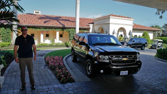 The vehicles for President Donald Trump's motorcade and a U.S. Secret Service agent are seen at the Trump National Golf Club, Friday, Nov. 24, 2017, in Jupiter, Fla.