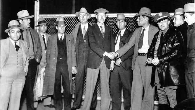 Jeff Meers and Jose Carrasco shake hands at the international boundary at the middle of the Santa Fe Street Bridge in the early morning hours of April 20, 1933. The two prisoners were exchanged by authorities from the United States and Mexico.