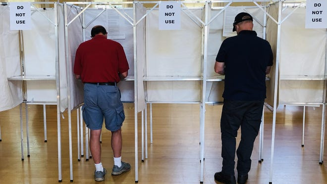 Timothy Connors, left, and Pete Donaher keep one empty booth between them as they vote in the auditorium at the Kennebunk Town Hall on Tuesday, July 14, 2020.