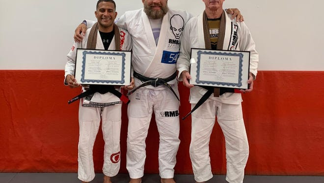Carlos Diaz, left, and Larry Bartenfelder, right, hold their diplomas as they pose with head instructor Rodrigo Mendes at RMBJJ Academy in Delray Beach, which teaches Brazilian jiujitsu. The two men recently received their black belts in the sport.