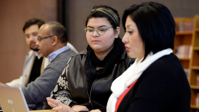 Affordable Care Act health insurance marketplace navigator Leticia Chaw, right, helps Jennifer Sanchez with information on how to re-enroll in a  health insurance plan on Nov. 14, 2014, in Houston.