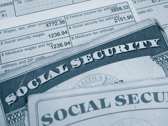 Two Social Security cards are at the top of a W2 tax form, showing tax on wages paid.