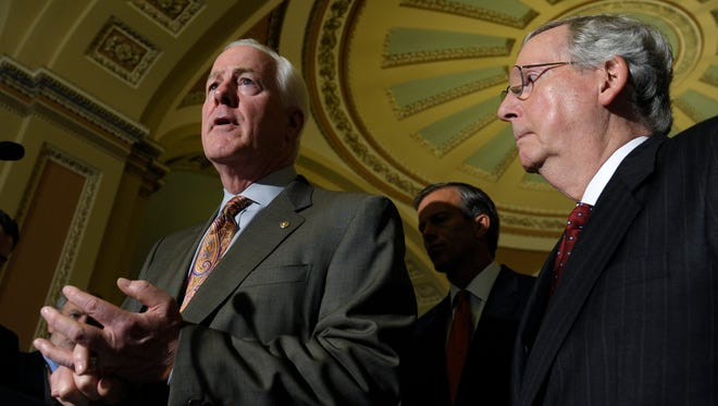 Senate Minority Leader Mitch McConnell of Ky., right, listens as Sen. John Cornyn, R-Texas, left, speaks to reporters following a policy luncheon on Capitol Hill.