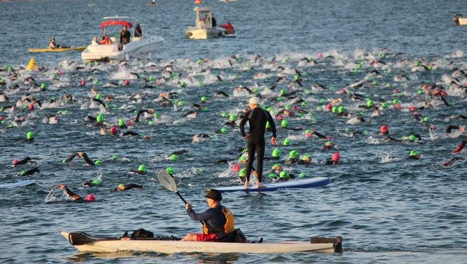Volunteers float nearby as participants compete in Ironman 70.3 St. George