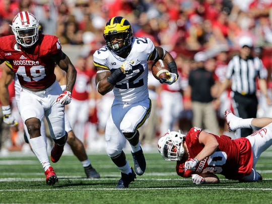 Michigan running back Karan Higdon, center, runs between Indiana defenders Greg Gooch, left, and Chase Dutra during the first half an NCAA college football game in Bloomington, Ind., Saturday, Oct. 14, 2017. (AP Photo/AJ Mast)