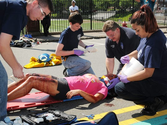 "From left, Nutley Volunteer Emergency and Rescue Squad volunteer Nick Gould, volunteer EMT Collin Keating, EMS coordinator Mike Rossi, and volunteer EMT Christina Rivera, prepare to move  ""injured"" Nutley High School student Alyssa Roccano to an ambulance in May 2012 during a high school demonstration."