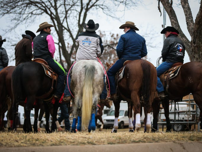 Riders warm up their horses for team roping during