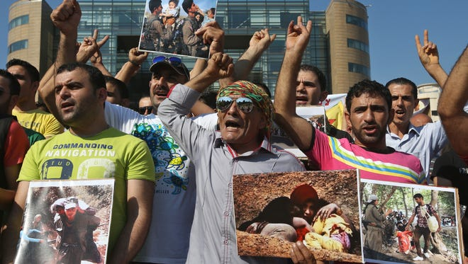 Kurdish citizens who live in Lebanon shout slogans and hold photographs of Kurdish fighters helping Kurds and Yazidis when they had to flee their villages, during a demonstration against militants who refer to themselves as the Islamic State, in front the UN building, in downtown Beirut, Lebanon, on Monday Sept. 15, 2014. An activist group and a Kurdish official say heavy clashes are taking place in northeastern Syria, with Kurdish fighters capturing about a dozen villages from Islamic militants. Kurdish fighters and members of the Islamic State group have been fighting each other for more than a year in northern Syria.